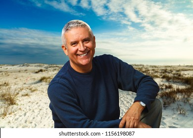 Handsome middle age man outdoor portrait with a dunes beach background.
