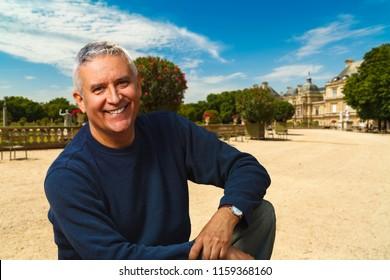 Handsome middle age man outdoor portrait with a Paris cityscape background.