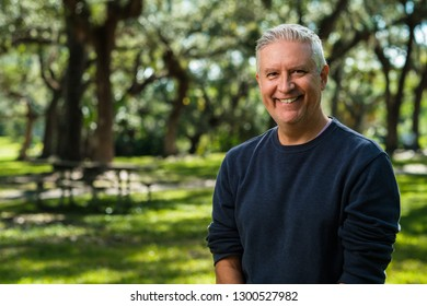 Handsome middle age man outdoor portrait in a park.