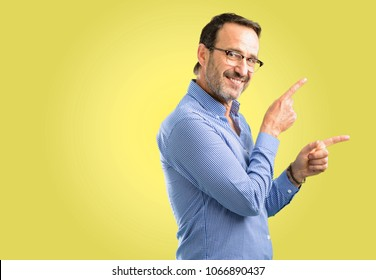 Handsome middle age man pointing away side with finger