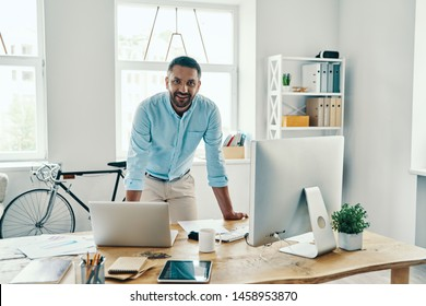 Handsome middle age man in smart casual wear looking at camera and smiling while standing in the office