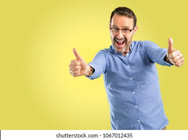 Handsome middle age man stand happy and positive with thumbs up approving with a big smile expressing okay gesture