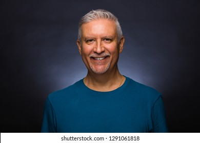 Handsome middle age man studio portrait with a gray background.