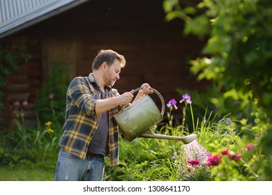 Handsome middle age man watering flowers in the yard in the summer. Gardening and floriculture.