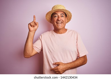 Handsome middle age man wearing summer hat standing over isolated pink background pointing finger up with successful idea. Exited and happy. Number one.