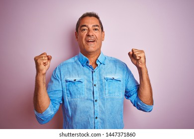 Handsome middle age man wearing blue denim shirt standing over isolated pink background screaming proud and celebrating victory and success very excited, cheering emotion