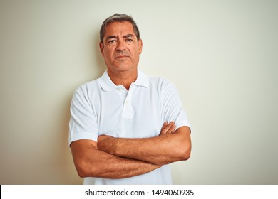 Handsome middle age man wearing polo standing over isolated white background skeptic and nervous, disapproving expression on face with crossed arms. Negative person.