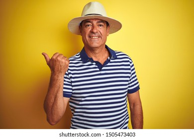 Handsome middle age man wearing striped polo and hat over isolated yellow background smiling with happy face looking and pointing to the side with thumb up.