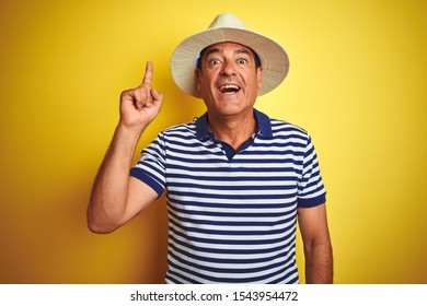 Handsome middle age man wearing striped polo and hat over isolated yellow background pointing finger up with successful idea. Exited and happy. Number one.