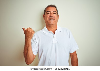 Handsome middle age man wearing polo standing over isolated white background smiling with happy face looking and pointing to the side with thumb up.