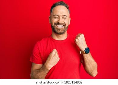 Un bel homme d'âge moyen en t-shirt rouge décontracté célébrant son succès avec surprise et surprise, les bras levés et les yeux fermés
