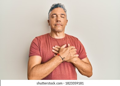 Handsome middle age mature man wearing casual clothes smiling with hands on chest, eyes closed with grateful gesture on face. health concept.