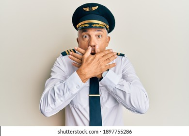 Handsome middle age mature man wearing airplane pilot uniform shocked covering mouth with hands for mistake. secret concept.