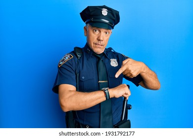 Handsome middle age mature man wearing police uniform in hurry pointing to watch time, impatience, upset and angry for deadline delay