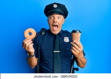 Handsome middle age mature police man eating donut and drinking coffee celebrating crazy and amazed for success with open eyes screaming excited.