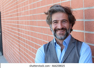 Handsome middle age Mediterranean man in a studio portrait on a red brick wall background smiling with copy space