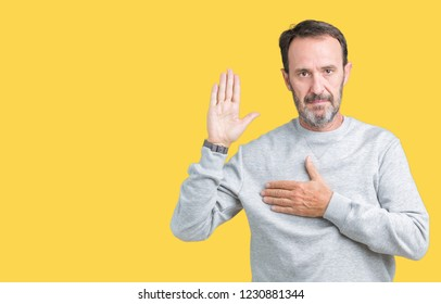 Handsome middle age senior man wearing a sweatshirt over isolated background Swearing with hand on chest and open palm, making a loyalty promise oath