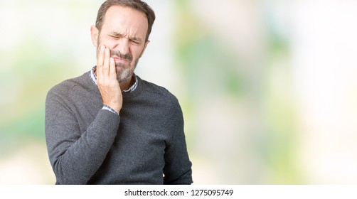 Handsome middle age senior man wearing a sweater over isolated background touching mouth with hand with painful expression because of toothache or dental illness on teeth. Dentist concept.
