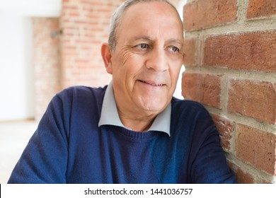 Handsome middle age senior man smiling cheerful, happy and positive leaning over bricks wall outdoors