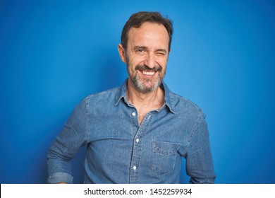 Handsome middle age senior man with grey hair over isolated blue background winking looking at the camera with sexy expression, cheerful and happy face.