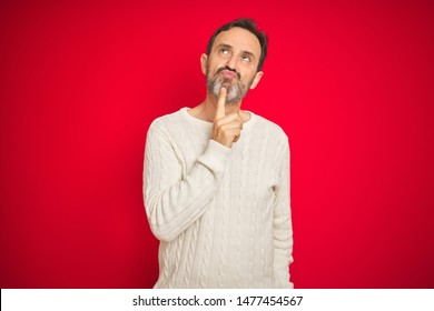 Handsome middle age senior man with grey hair over isolated red background Thinking concentrated about doubt with finger on chin and looking up wondering