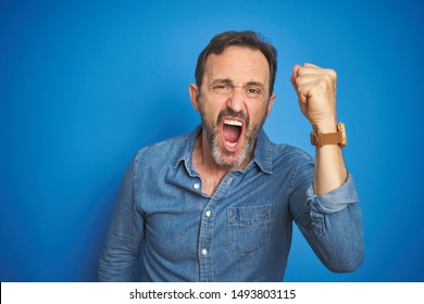 Handsome middle age senior man with grey hair over isolated blue background angry and mad raising fist frustrated and furious while shouting with anger. Rage and aggressive concept.