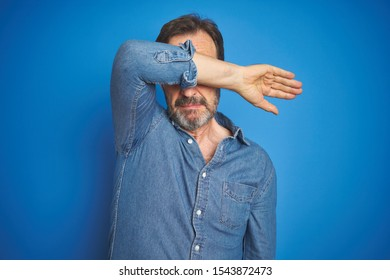 Handsome middle age senior man with grey hair over isolated blue background covering eyes with arm, looking serious and sad. Sightless, hiding and rejection concept