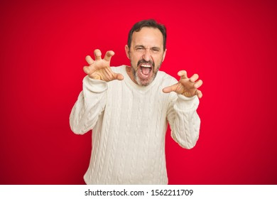 Handsome middle age senior man with grey hair over isolated red background smiling funny doing claw gesture as cat, aggressive and sexy expression