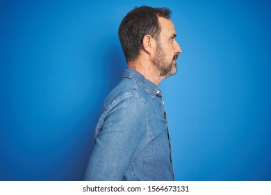 Handsome middle age senior man with grey hair over isolated blue background looking to side, relax profile pose with natural face and confident smile.