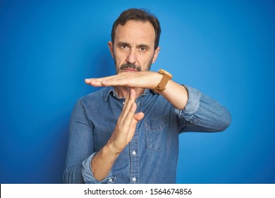 Handsome middle age senior man with grey hair over isolated blue background Doing time out gesture with hands, frustrated and serious face