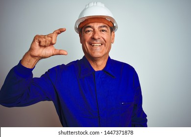 Handsome middle age worker man wearing uniform and helmet over isolated white background smiling and confident gesturing with hand doing small size sign with fingers looking and the camera.