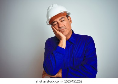 Handsome middle age worker man wearing uniform and helmet over isolated white background thinking looking tired and bored with depression problems with crossed arms.