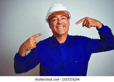 Handsome middle age worker man wearing uniform and helmet over isolated white background smiling cheerful showing and pointing with fingers teeth and mouth. Dental health concept.