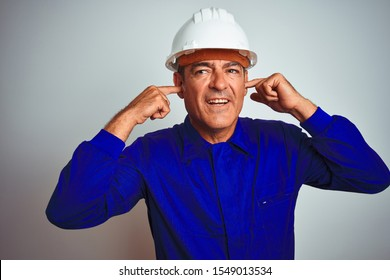Handsome middle age worker man wearing uniform and helmet over isolated white background covering ears with fingers with annoyed expression for the noise of loud music. Deaf concept.