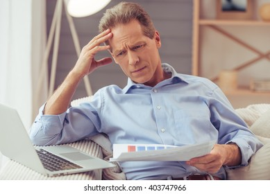Handsome middle aged businessman in classic shirt is using a laptop and examining documents while working at home