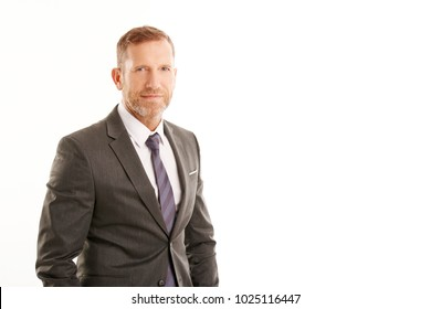 Handsome middle aged businessman wearing suit and looking at camera while standing at isolated white background with copy space.
