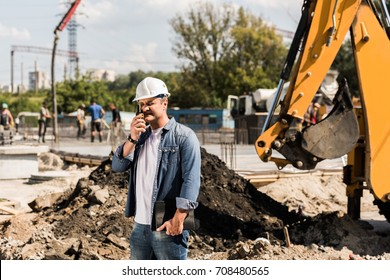 handsome middle aged construction worker with walkie talkie