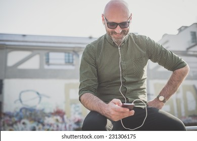 handsome middle aged man listening to music in the city