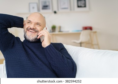 Handsome middle aged man in mustache and beard with hand behind head while looking up in conversation on cell phone indoors