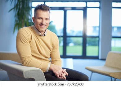 A handsome middle aged man sitting on sofa and relaxing.