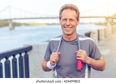Handsome middle aged man in sports uniform is warming up, holding a jumping rope and smiling during morning run