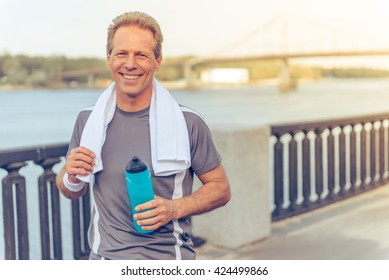 Handsome middle aged man in sports uniform is holding a bottle of water, looking at camera and smiling, resting during morning run