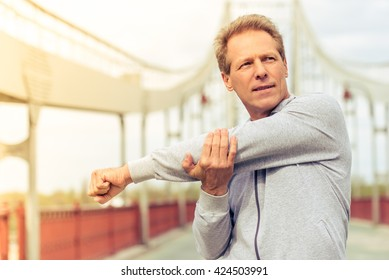 Handsome middle aged man in sports uniform is looking away and warming up during morning run