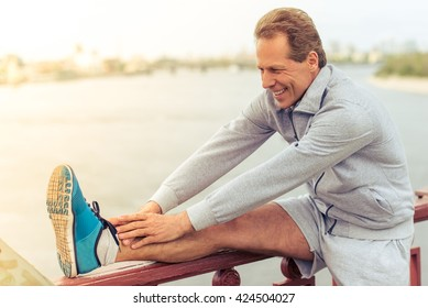 Handsome middle aged man in sports uniform is stretching leaning on bridge and smiling during morning run