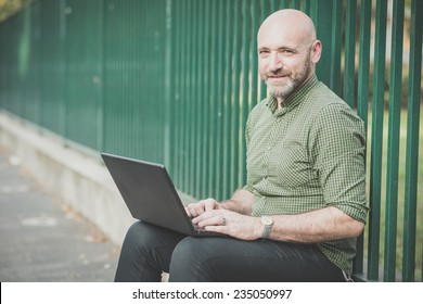 handsome middle aged man using notebook in the city