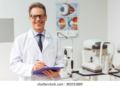 Handsome middle aged ophthalmologist making notes and smiling while standing in his office