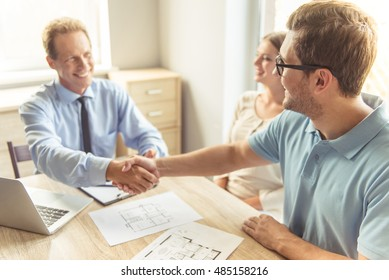 Handsome middle aged realtor in classic shirt and eyeglasses is shaking hands with his clients and smiling while sitting in office
