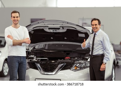 Handsome middle aged salesman is showing a car engine to handsome young customer in a motor show. Both are looking at camera and smiling