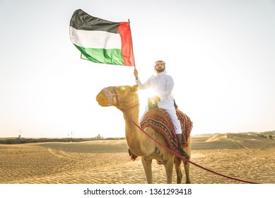 Handsome middle eastern man with kandura and gatra riding on a camel in the desert