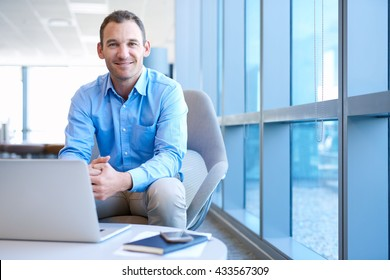 Handsome middle-aged business executive sitting in a bright modern office, smiling at the camera with a trustworthy expression